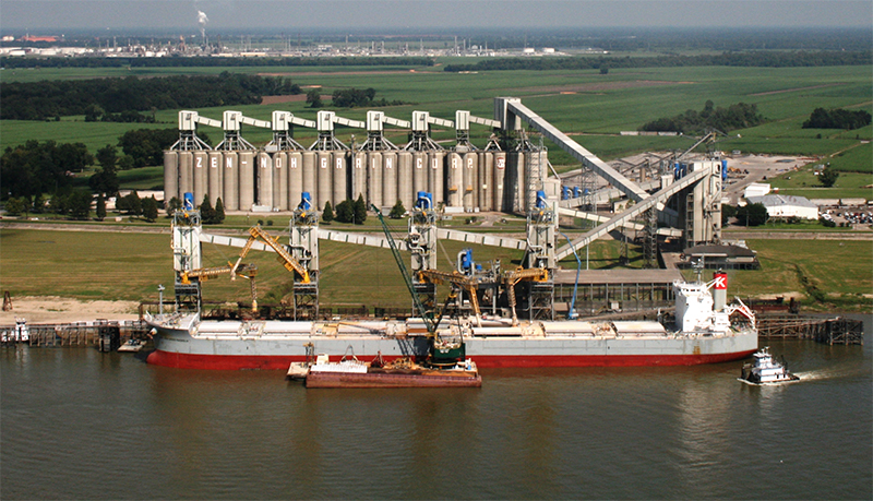photo of a CGB Grain port that has a red cargo ship waiting to be loaded and behind it are bronze colored grain silos which keep the grain stored.