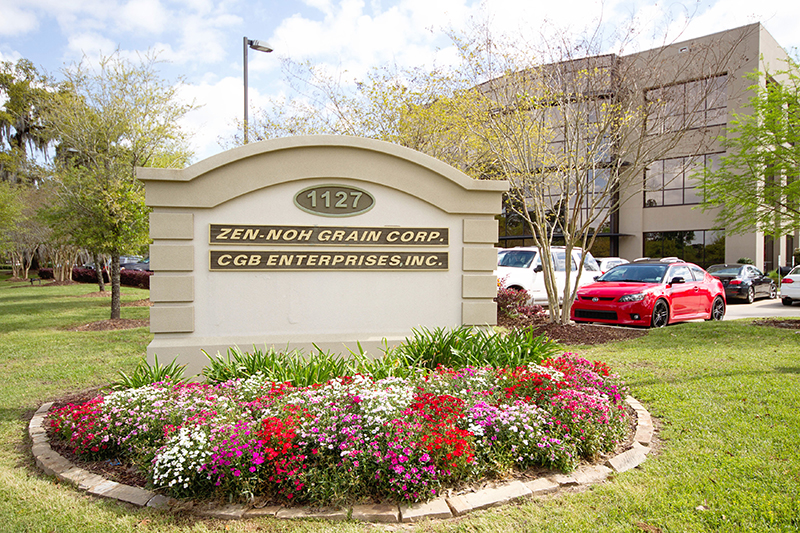 photo of a stucco sign in front of a large building that reads Zen-Noh Grain Corp and CGB Enterprises, Inc. The sign is surrounded by trees and flowers in differen colors such as white, red, and pink.